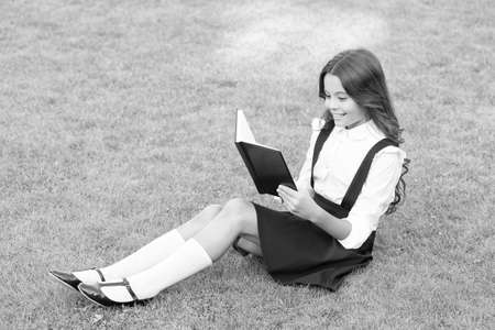 hardworking child with book. concept of education and reading. development of the imagination. cute girl read book. happy preschool girl with book in school yard. back to school