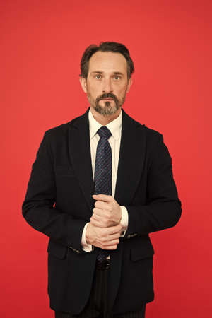 Bespoke suit flatters every wearer. Perfect suit for every type of guy. Man handsome mature fashion model wear fashionable suit on red background. Suit imbue sense of confidence of gentlemen
