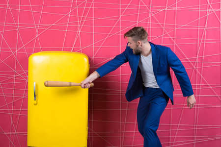 confident businessman in suit. Business fashion. Businessman with bat hit yellow fridge. aggressive man. Feel the success. Male formal fashion. man in stylish jacket. Hungry attack concept