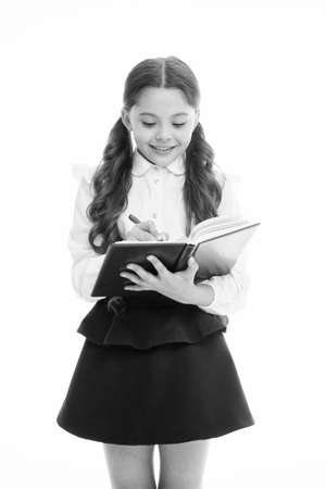 Schoolgirl write daily schedule notepad isolated on white. Little child hold textbook with pen. Plan for week. Home schooling education. Adorable bookworm planning her studying schedule for week