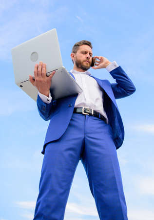Always in touch. Communicating skill. Guy formal suit modern technology manager entrepreneur answer phone call. Man well groomed businessman holds laptop while speak phone blue sky background