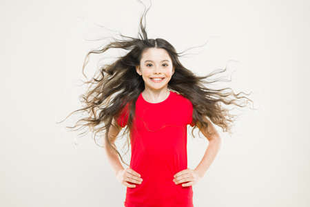 Things you doing to damage your hair. Girl adorable kid long wavy hair yellow background. Wind can also damage hair. Strong persistent winds can create tangles and snags in wavy and curly long hair Stock fotó