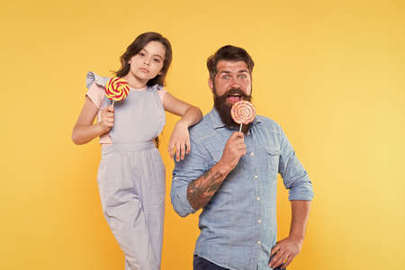 Happy holidays. Sweet childhood. When children seem hard to please. Daughter and father eat sweet candy. Bearded man and cute sweet baby. Loving daddy and small girl eating lollipop. Summer vacation
