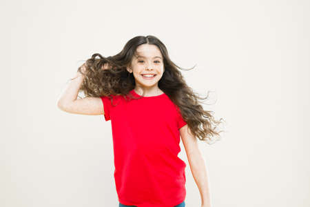 Strong persistent winds can create tangles and snags in wavy and curly long hair. Things you doing to damage your hair. Girl adorable kid long wavy hair yellow background. Wind can also damage hair