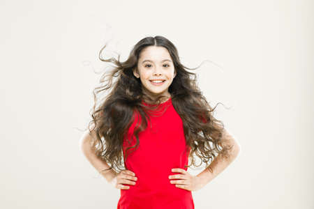 Wind can also damage hair. Strong persistent winds can create tangles and snags in wavy and curly long hair. Things you doing to damage your hair. Girl adorable kid long wavy hair yellow background Stock fotó