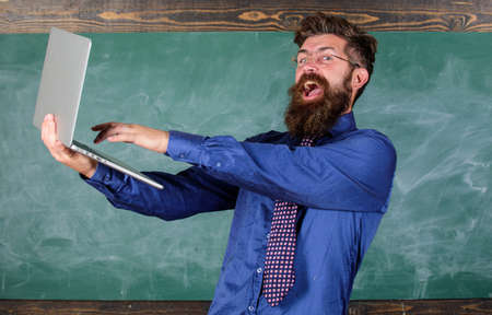 Successful examination. Pass test online. Teacher bearded happy man with modern laptop passed test online chalkboard background. Hipster teacher eyeglasses hold laptop passed distance knowledge check