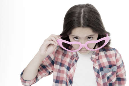 Girl cute big heart shaped glasses isolated white background. Child girl looks wondered or surprised. Are you serious. Kid peeking out of glasses, copy space. Child can not believe her eyes