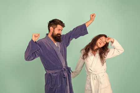 Half awake. Couple in love look sleepy in morning. Sleepy woman and hipster stretch and yawn blue background. Early morning time. Being tired and sleepy. Home clothing. Awakening. Feeling sleepy