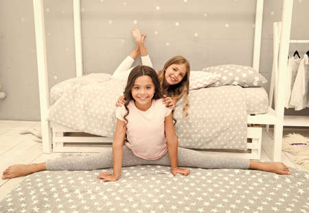Lockdown with usefulness. Exercising and stretching body. Improve flexibility. Evening stretching. Cute gymnast practice split before bedtime. Kids sisters prepare go to bed. Girls cute pajamas