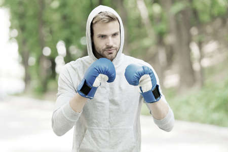 Man athlete on concentrated face with sport gloves practicing boxing punch, nature background. Boxer hood head practices jab punch. Sportsman boxer training with boxing gloves 版權商用圖片