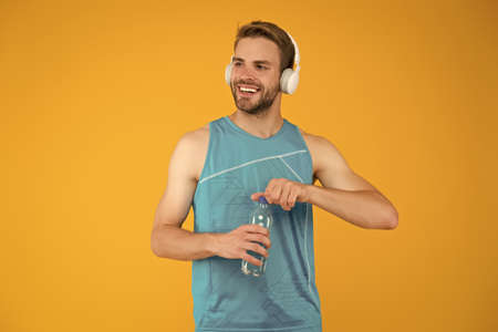 Celebrating health. Healthy man open water bottle. Fitness coach wear headphones. Water and hydration. Health benefits. Increasing water level and health. Fitness for health resolution