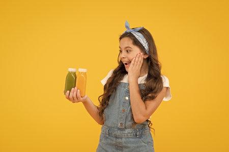 Buy food. Supermarket promotion. Living healthy life. Vitamin juice. Fresh smoothie. Girl drinking orange fresh smoothie. Vegetarian concept. Smiling kid hold fruit smoothie bottles. Healthy food 版權商用圖片