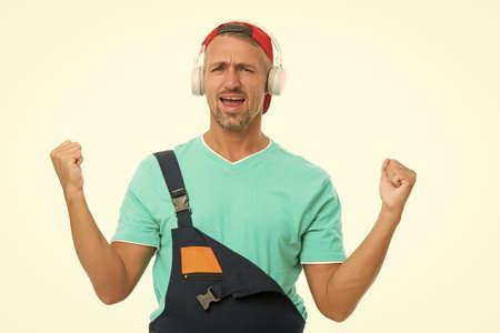 Listen music for motivation. Cheerful worker. Everything better with favorite music. Enjoying audio book. Modern earphones concept. Audio education. Audio track. Man builder handyman listening audio 版權商用圖片