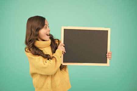 Cute schoolgirl with blackboard. Advertisement. Notice information. Notification concept. Little girl hold blank chalkboard place for notification. Read this notification. Informing about event