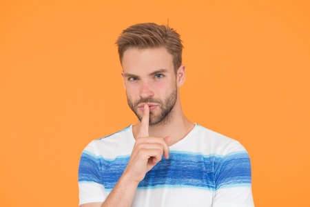 Zip your lip. Trying to keep it a secret. Secret spy or agent with silence gesture on yellow background. Handsome man keeping finger on mouth with secret. Confidential information and top secret