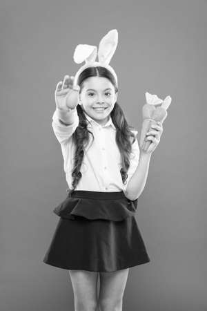 Easter eggs. Happy easter. Origins of Easter Traditions. Small girl bunny ears. Kid on easter egg hunt. Adorable happy child hold eggs. Spring holiday. Little schoolgirl in rabbit ears hold carrot