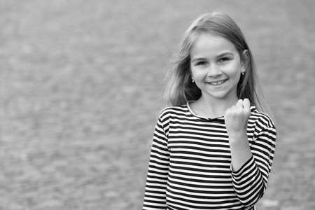 Girl power. Happy girl show fist outdoors. Beauty look of child girl. Little kid smile in stripy top. Casual style. Summer fashion. Trendy wardrobe. Hair salon. Stunning and gorgeous, copy space 版權商用圖片