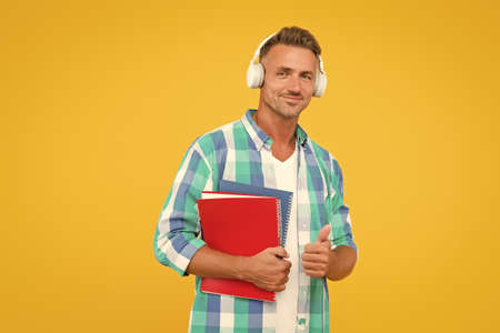 adult student hold notebook. man with folder in headphones. online education. man hold book for notes while listen ebook. lets write in notepad. handsome school or university teacher. thumb up