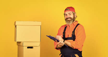 Renovation preparation. Unpacking moving boxes. Delivering packages. Bearded man courier hold boxes. Moving to new apartment. Post service. Bearded loader in uniform. Real estate. Moving day