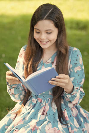 For your reading pleasure. Happy girl read book in summer park. Small child enjoy reading outdoors. Summer reading list. Developing imagination. Reading is fun