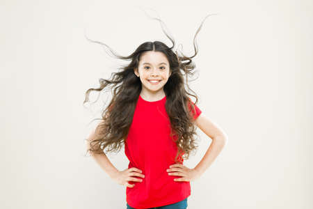 Wind can also damage hair. Girl adorable kid long wavy hair yellow background. Things you doing to damage your hair. Strong persistent winds can create tangles and snags in wavy and curly long hair Stock fotó