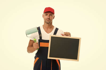 Training that transforms beginner into skilled professional. Painter hold blackboard and paint roller. Decorator training course. Training school. Training in painting and decorating, copy space