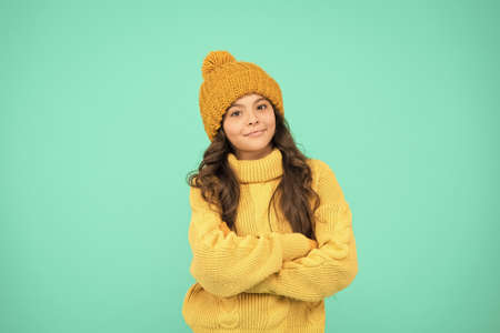 nice day. keep yourself warm. little girl favorite sweater. hat and mittens accessory. happy child turquoise wall. no flu. get ready for winter. winter holiday. homemade knit. cold season fashion Banque d'images