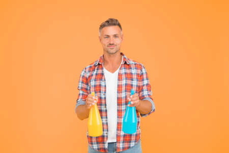 Cleaning solution. Happy guy hold spray bottles. Cleaning man yellow background. Cleaning service. Using spray disinfectants. Disinfecting home. Domestic cleaning. Household cleaners