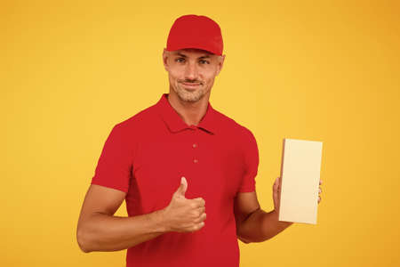 Perfect delivery. Delivery man hold box yellow background. Package boy give thumbs up in red uniform. Parcel delivery. Express delivery courier service. Parcel post package. Deliver it, copy space