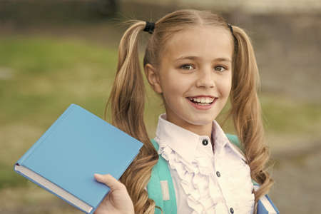 Book is uniquely portable magic. Happy schoolgirl hold book outdoors. Little reader. School library. Literature study. Reading habit. Book shop. Education and knowledge. Book you cant resist