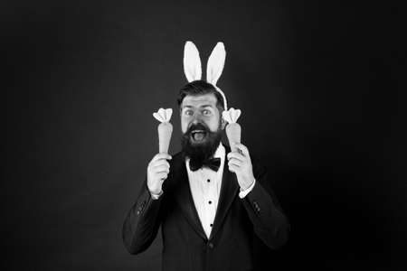 Handsome man wear bunny costume accessory. Celebration Easter holiday. Carrot is good for your teeth. Easter day. Event host. Celebrate Easter. Bearded man with long ears. Businessman with long ears