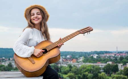 trendy looking kid girl play acoustic guitar, music