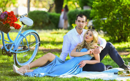 nice summer holiday. girl and man travel by retro bicycle. couple in love drinking wine during romantic dinner in park. romantic picnic of couple in love. family relationship and friendship Foto de archivo