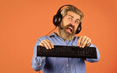 Superior performance. Graphics settings pushed to limit. Play computer games. Man bearded hipster gamer headphones and keyboard. Gaming addiction. Online gaming. Modern leisure. Run any modern game