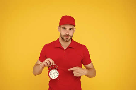 countdown. deadline and discipline. punctual delivery man. on-time delivery. man in uniform pointing finger alarm clock. Moving Office Service. time management concept. what time is it