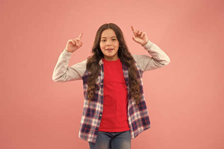 Follow your dream. Little child pointing up pink background. Small child in casual wear. Beauty look of cute child girl. Fashion trend. Trendy style. Child care and childhood. Childrens day