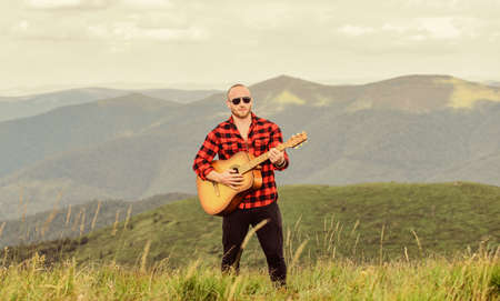 Music for soul. Playing music. Sound of freedom. In unison with nature. Acoustic music. Musician hiker find inspiration in mountains. Keep calm and play guitar. Man with guitar on top of mountain 版權商用圖片