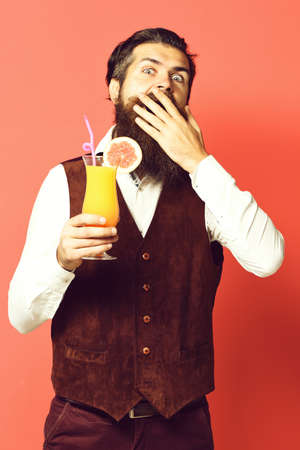 cocktail in vintage suede leather waistcoat on red studio background. surprised handsome bearded man