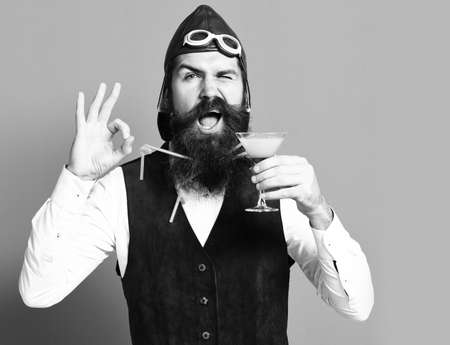 happy face holding glass of alcoholic beverage in vintage suede leather waistcoat with hat and glasses on red studio background. happy handsome bearded pilot