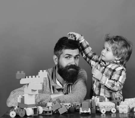 Family with curious faces build toy cars out of colored construction blocks. Childhood and playing. Kid puts green toy on dads head