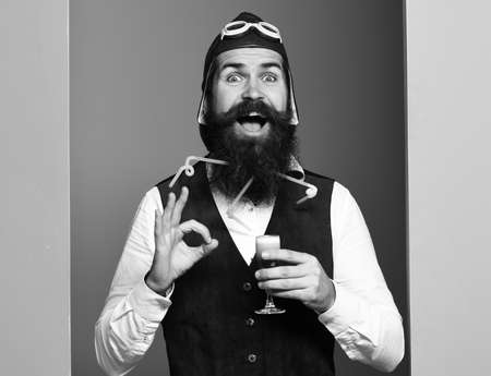 smiling face holding glass of alcoholic shot in vintage suede leather waistcoat with hat and glasses on studio background. smiling handsome bearded pilot