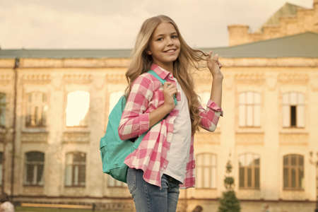 Teen with backpack. Stylish smiling schoolgirl. Girl little fashionable schoolgirl carry backpack school building background. Schoolgirl daily life. School club. Modern education. Private schooling