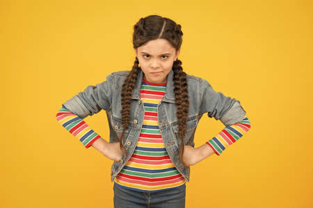 In bad humor. Moody little child yellow background. Little baby wear braided hairstyle. Little girl in casual style. Little kid with hands on hips. Trendy fashion. Stylish trends. Hair salon