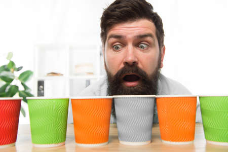 Curious man looks on colorful coffee cups. Color your day. Different types of coffee drinks in cafe menu. large assortment. assortment of coffee. energy drink assortment. bearded man want to drink