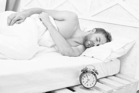Man waking up early morning ringing alarm clock, deep sleep concept