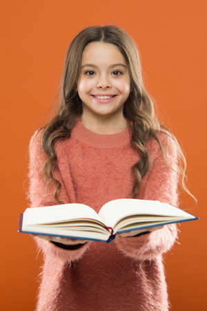 Girl hold book read story over orange background. Child enjoy reading book. Book store concept. Wonderful free childrens books available to read. Reading practice for kids. Childrens literature