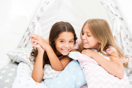 Sisters share gossips having fun at home. Pajamas party for kids. Cozy place tipi house. Sisters or best friends spend time together lay in tipi house. Girls having fun tipi house. Girlish leisure