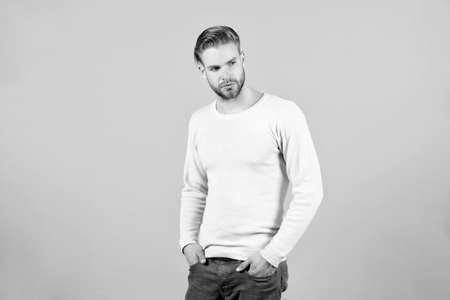 Man with beard unshaven guy looks handsome and well groomed casual clothes. Guy bearded and attractive with hairstyle. Masculinity concept. Man with bearded strict concentrated face, grey background