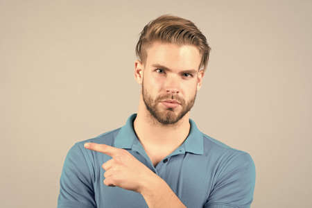 Handsome young man in tshirt looking at camera pointing away