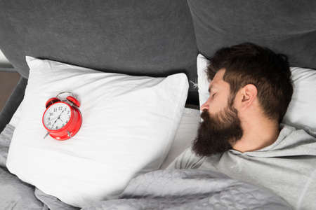 Man bearded hipster sleepy face in bed with alarm clock. Problem with early morning awakening. Get up with alarm clock. Overslept again. Tips for waking up early. Tips for becoming an early riser